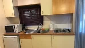 Stort kylskåp, mikrovågsugn och grytor/köksredskap