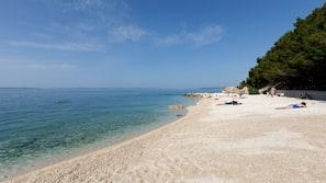 På stranden, hvit sand, strandhåndklær og snorkling
