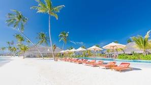 On the beach, white sand, sun-loungers, beach umbrellas