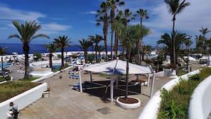 On the beach, black sand, sun loungers, beach umbrellas