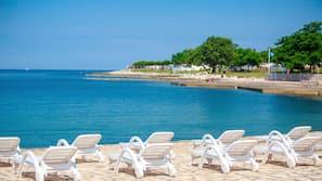 In Strandnähe, weißer Sandstrand, Sonnenschirme, Strandbar