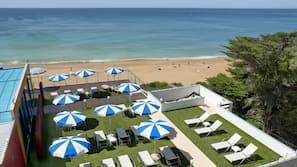 Am Strand, weißer Sandstrand, Strandtücher, Strandbar