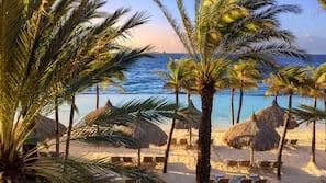 Een privéstrand, wit zand, ligstoelen aan het strand, parasols