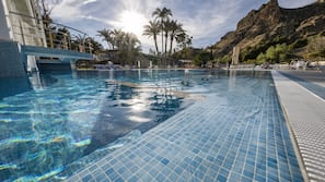 Una piscina cubierta, una piscina al aire libre, sombrillas, tumbonas