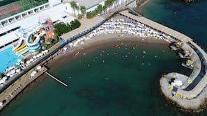 Een privéstrand, ligstoelen aan het strand, parasols, strandlakens