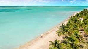 Na praia, areia branca, barracas de praia de cortesia, espreguiçadeiras