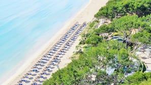Sulla spiaggia, sabbia bianca, ombrelloni, teli da spiaggia