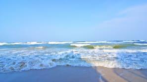 Am Strand, weißer Sandstrand, Sonnenschirme, Strandtücher