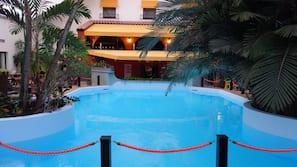 Een binnenzwembad, ligstoelen bij het zwembad