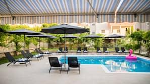 Seasonal outdoor pool, open 9 AM to 10 PM, pool umbrellas, pool loungers