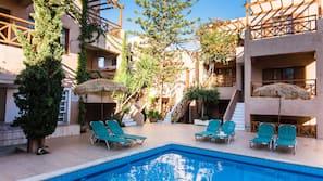 Seasonal outdoor pool, open 9 AM to 8:00 PM, pool umbrellas