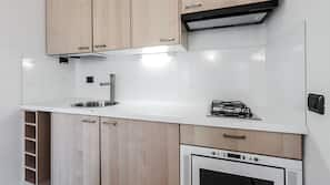 Een koelkast, een oven, een kookplaat, kookgerei, borden en bestek