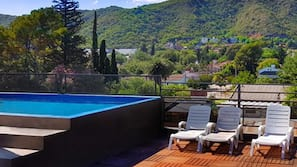 Outdoor pool, open 10:00 AM to 9:00 PM, pool umbrellas