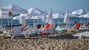 Am Strand, Liegestühle, Sonnenschirme, Volleyball