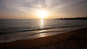 In Strandnähe, weißer Sandstrand, Liegestühle, Sonnenschirme