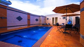Outdoor pool, open 10:00 AM to 7:00 PM, pool umbrellas