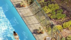 Een buitenzwembad, parasols voor strand/zwembad