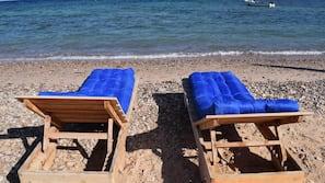 Na praia, espreguiçadeiras, prática de mergulho autônomo