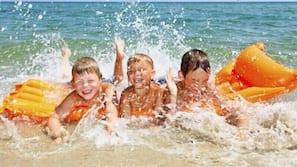 Una spiaggia nelle vicinanze, sabbia bianca, lettini da mare, pallavolo