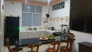 Een oven, een kookplaat, een rijstkoker, kookgerei, borden en bestek