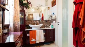 Een bad/douchecombinatie, een bubbelbad, een bidet, handdoeken