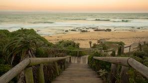Perto da praia, areia preta, espreguiçadeiras, guarda-sóis