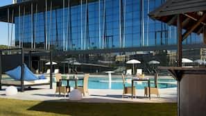 Una piscina cubierta, una piscina al aire libre, sombrillas
