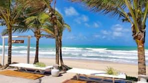 Na praia, areia branca, espreguiçadeiras, guarda-sóis