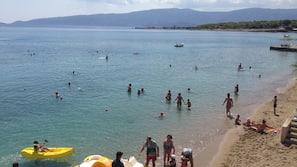 Plage privée, parasols, serviettes de plage, planche à voile