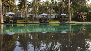 Een buitenzwembad, een infinity pool, parasols voor strand/zwembad