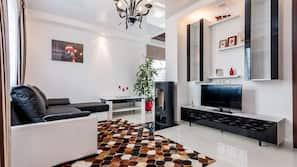 En 105-tommers flatskjerm-TV med kabel-kanaler samt peis