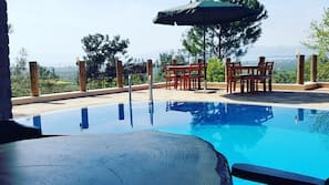 Seasonal outdoor pool, open 9:00 AM to 6:00 PM, pool umbrellas