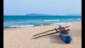 Aan het strand, wit zand, parasols, strandlakens