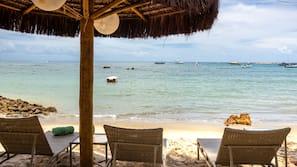 Praia particular, areia branca, espreguiçadeiras, guarda-sóis