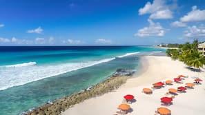 On the beach, white sand, beach towels, windsurfing