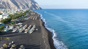 On the beach, black sand, sun loungers, beach umbrellas
