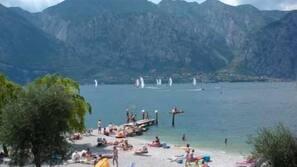 Vlak bij het strand, ligstoelen aan het strand, strandlakens, waterskiën