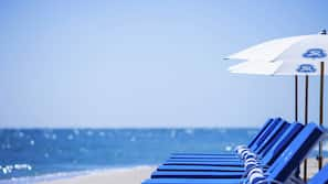 On the beach, white sand, beach cabanas, sun loungers