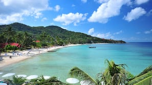 Trên bãi biển, ghế dài tắm nắng, dù trên bãi biển, khăn tắm biển