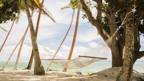 On the beach, white sand, sun-loungers, beach towels