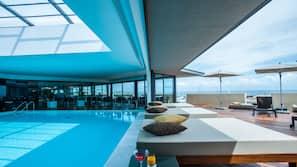 Een binnenzwembad, een buitenzwembad en ligstoelen