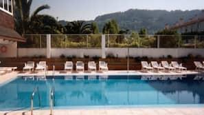 Una piscina cubierta, piscina al aire libre, tumbonas