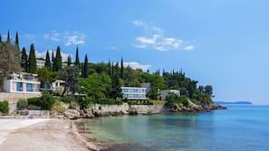 Aan het strand, ligstoelen aan het strand, parasols, een strandbar