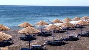 Una spiaggia nelle vicinanze, sabbia scura, lettini da mare, ombrelloni