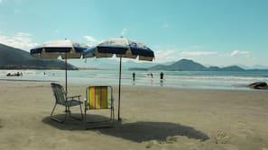 Perto da praia, areia branca, guarda-sóis, toalhas de praia