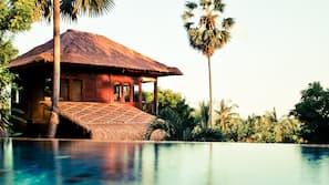 Outdoor pool, an infinity pool, pool umbrellas, pool loungers