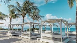 Aan het strand, wit zand, ligstoelen aan het strand, strandlakens