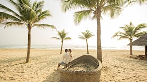 Nær stranden, hvit sand, solsenger og parasoller