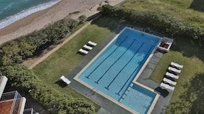 Una piscina al aire libre de temporada, sombrillas, tumbonas