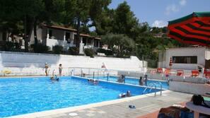 Piscina all'aperto, una piscina sportiva, ombrelloni da piscina, lettini